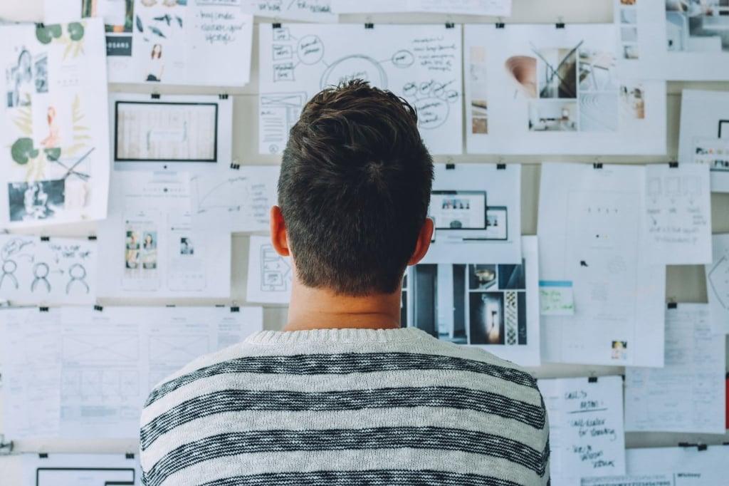 Homme devant un tableau blanc avec feuilles d'analyse