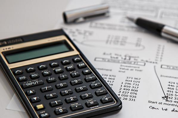 Tableau de financement imprimé posé à côté d'une calculatrice et d'un stylo à plume