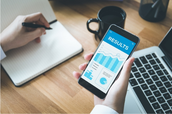 bureau gros plan sur des mains tenant un smartphone qui affiche les graphiques mesurant des résultats